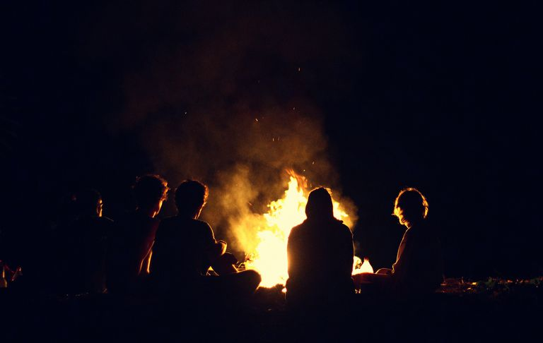 Modern humans continue the ancient tradition of gathering around a campfire.